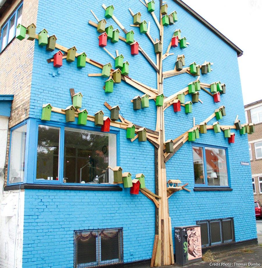 Nichoirs à oiseaux originaux sur façade de maison bleue